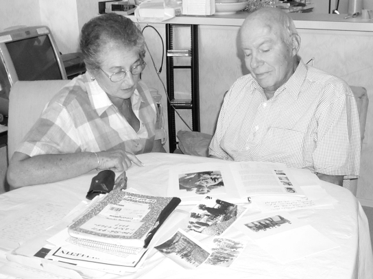 Harry Glixon and his wife, Lorraine, look at the book he wrote for his grandchildren and some old war pictures involving his time as a POW of the Germans during World War II.