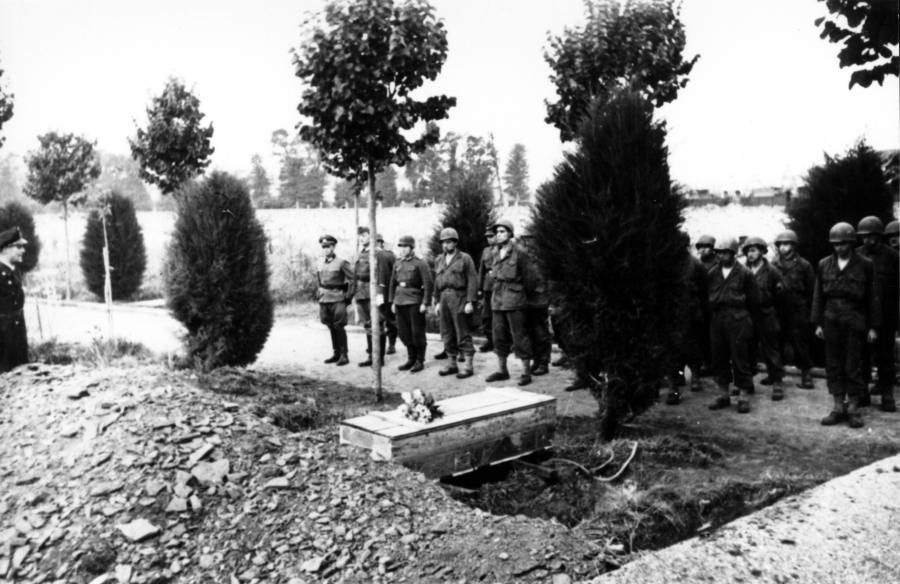 Members of the 94th Infantry Division, captured by the Germans at Lorient, France, stand in ranks during a funeral for one of their own held while they were POWs. Note the flowers on the crudely made wooden casket and the German officer standing at the far left side in the forefront.