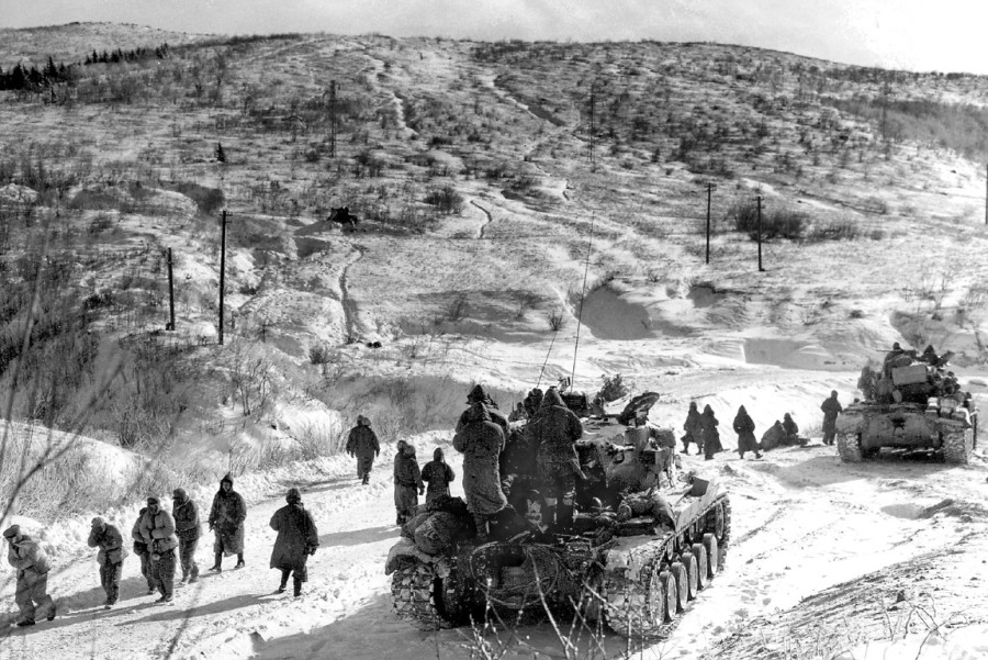 Tanks attached to Company C, 1st   Battalion, 7th  Regiment, 1st Marine   Division moved around a destroyed bridge   south of Kotgo-ri on Dec. 9, 1950. This   picture was taken during the division's   historic march up and back to the Chosin   Reservoir along the North Korean-Chinese   border in the early months of the Korean   War. Note the Chinese prisoners being herded to the rear for questioning.