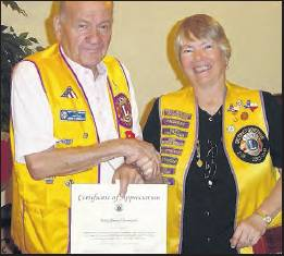 SUN FILE PHOTO    North Port Lion Hank Chiminiello receives a certificate of appreciation, chevron pin and 50-year membership patch from Lions president Penny Gregrich in January 2011. Chiminiello was recognized by Lions Clubs International for his 50›years of continuous membership.