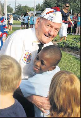 SUN FILE PHOTO    Hank Chiminiello, a World War›II veteran and longtime Glenallen Elementary School volunteer, receives a hug from student Jonah Monclerc in September 2010. Chiminiello was one of the honored guests at the North Port school's Freedom Celebration.