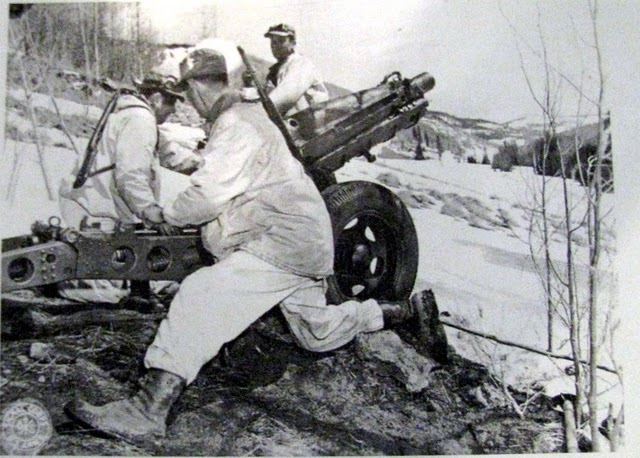 Two members of the 10th Mountain Division fire a 75 mm Howitzer during the attack on Mt. Belvedere when the division broke through the German lines on its way to northern Italy in February 1944.  U.S. Signal Corps Photo