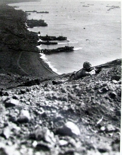 "A Marine takes aim at the enemy while in he background LSTs (Landing Ships) deposit more ""Leathernecks"" on the black-sandy beach of Iwo Jima below. Photo provided by Dick Honyak"