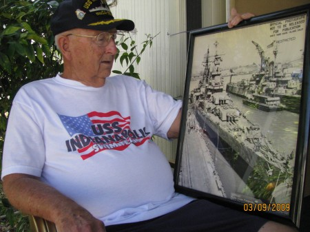 Jim Jarvis, a sailor aboard the U.S.S. Indianapolis, looks at an official picture of the ill-fated vessel. It was sunk by a Japanese submarine in the Philippine Sea a few days before the end of WW II and some 880 sailors perished. Sun photo by Don Moore
