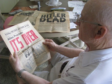 "Roland Petit of La Casa mobile home park in North Port looks at a ""Stars and Stripes"" proclaiming in screaming red letters: 'IT'S OVER."" On the table is another paper noting: ""HITLER DEAD."" Sun photo by Don Moore"