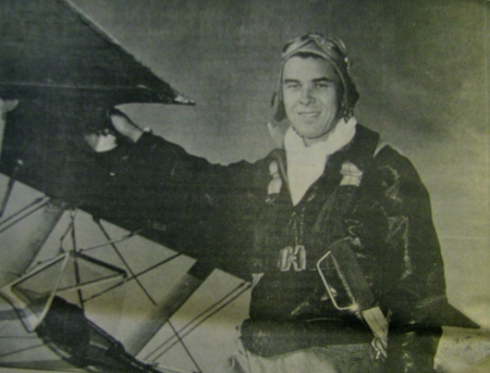 Flying Officer Bill Springer is pictured in his leather flying jacket and helmet standing on the wing of his Stearman advanced trainer. Photo provided