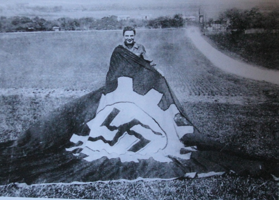Sannella holds a giant Nazi flag somewhere in Europe during World War II. Photo provided by Ted Sannella