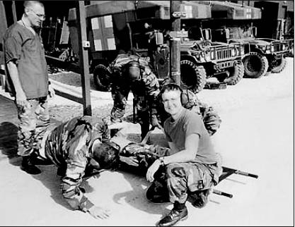 Dr. Arturo Rodriguez-Martin, at right, works with several soldiers in Bosnia practicing loading a wounded soldier onto a stretcher for transport in a helicopter. Photo provided