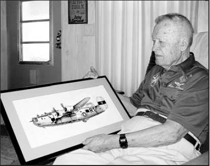 "Former 1st Lt. Adam Kubinciak, who lives in La Casa mobile home park in North Port, holds a picture of his B-24 ""Liberator"" ""Miss Liberty,"" that he flew during World War II. The picture of the plane was cross-stitched by Pat Pocock of Bungay, England, near where Kubinciak's bomber group was stationed."