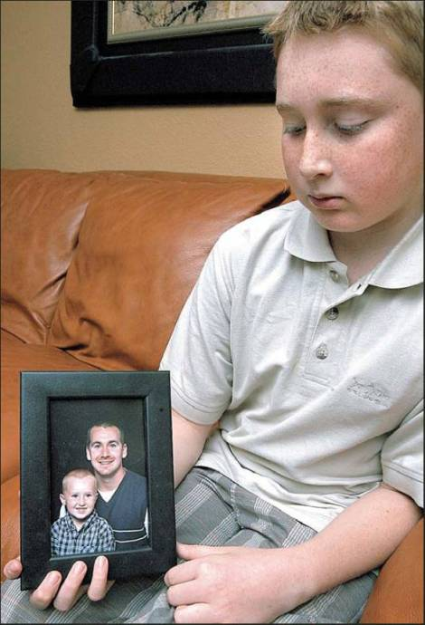 Slade Tully of North Port holds a picture of him and his dad, Green Beret Sgt. Michael Tully, who was killed by a roadside bomb near Baghdad on Thursday. The picture was taken several years ago. Sun photo by Kharli Rose