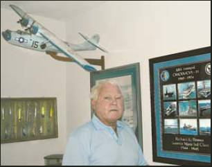 "Dick Brown was in charge of two 40-millimeter antiaircraft guns on the port side of the aircraft carrier USS Intrepid during World War II. The framed pictures are of the Intrepid. He also flew as part of a PBY ""flying boat"" crew, like the one above his head, late in the war.  Sun photo by Don Moore"