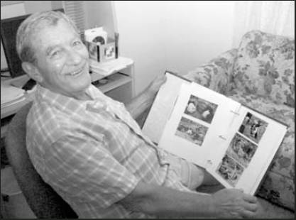 Ken Budd looks at a scrapbook of photos taken during his four trips to Guadalcanal since 1985 searching for his brother, Robert. Sun photo by Don Moore