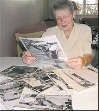 Winifred looks at magazines and other memorabilia from a lifetime ago when she was a poster girl for the WACs in World War II. Sun photo by Don Moore