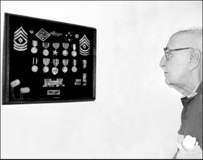 Vincent Carvalho of Rotonda looks at a shadowbox full of medals he received while serving in the Americal Division in the Pacific during World War II.