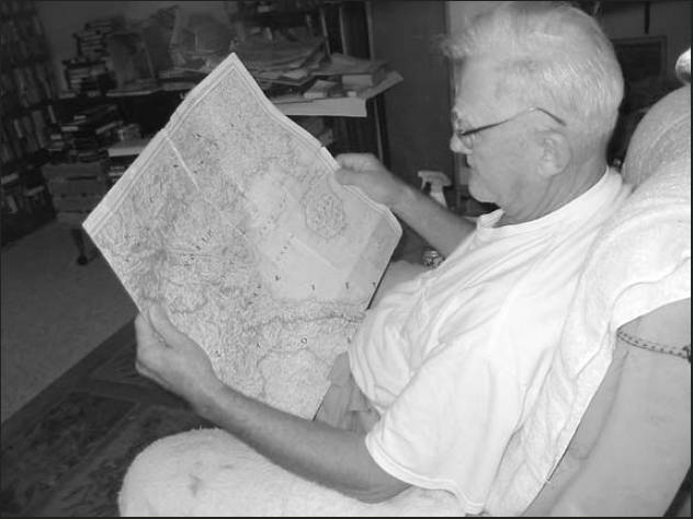 John Schoell looks at a map of Korea trying to find the two towns where his regiment landed during the war. Sun photo by Don Moore