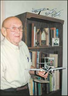 Col. Hal Johnson, who lives in southwest Florida, holds a model of an A-1 attack bomber like the one he flew in Vietnam. Sun photo by Don Moore