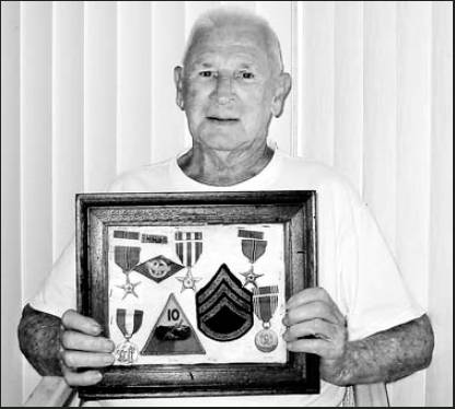 George Sutherland of Rotonda holds a shadowbox containing his Silver Star, two Bronze Stars for valor, a World War II Victory Medal and a Good Conduct Medal he received while serving as a tank commander in the 10th Armored Division in Europe during WWII. Sun photo by Don Moore