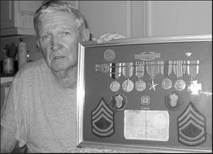 George Phillips of North Port is pictured with a shadow box full of his World War II medals and his sergeant stripes. He served in Gen. George Patton's 3rd Army. Sun photo by Don Moore