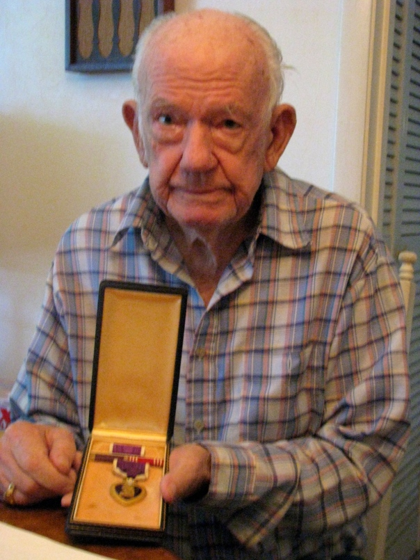 Bob Balch at 91 holds the Purple Heart medal he received after being injured when a shell from the 105 millimeter Howitzer he was firing hit a tree branch and showered the gun crew with deadly shrapnel. Two of the crew members were killed and Belch and another soldier were injured in the incident.