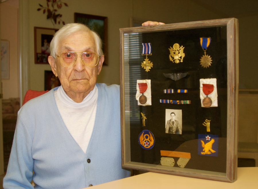Raynes holds a shadow box full of his World War II military medals, bars and patches that hangs on his office wall in La Casa. At the top left in the box is the Distinguished Flying Cross, just below the Medal of Honor for surviving 25 combat missions over Nazi-occupied Europe a lifetime ago. Sun photo by Mary Auenson