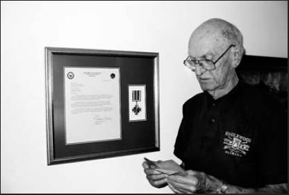 Jay FIsh holds one of several 2-inch square diaries he made from Chesterfield cigarette packages as he recorded life as a German PoW more than six days ago. His new DFC and commendation, framed by his son, is on his living room wall beside him. Sun photo by Don Moore
