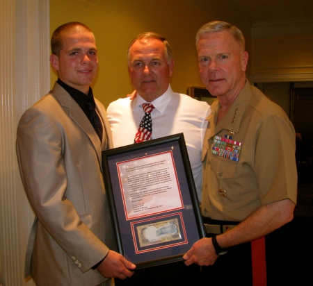 Randy Smith and his son, Brett, of Venice present a plaque to Marine Corps Commandant James Amos at a Semper Fi Fund Charity Golf Tournament at Boca Royale Golf and Country Club near Englewood on Friday. Sun photo by Don Moore