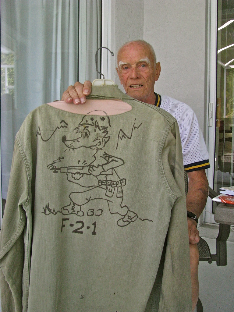 "Robb holds a cartoon drawing on the back of his old fatigue shirt, drawn by an unknown artist in his company. It shows a fox in Marine uniform depicting ""Fox Company,"" his unit."