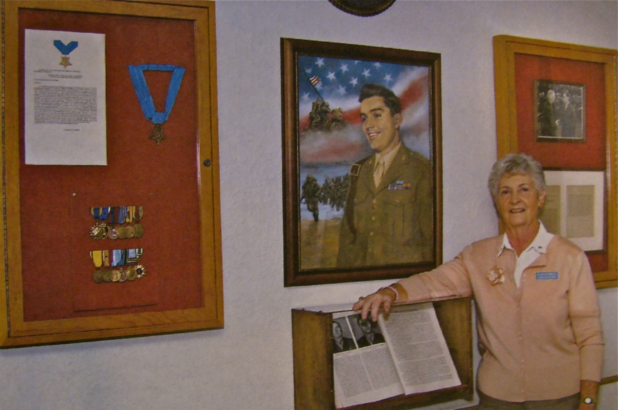 Joan Jacobson stands in front of a painting of her late husband, Douglas T. Jacobson when he was a 19-year-old Marine and received the Medal of Honor for his exploits on Iwo Jima during World War II. This display, including all his medals, are in the  entrance-way to the state veterans's nursing home in Port Charlotte, Fla. named in his honor. Sun photo by Lester Kuhn