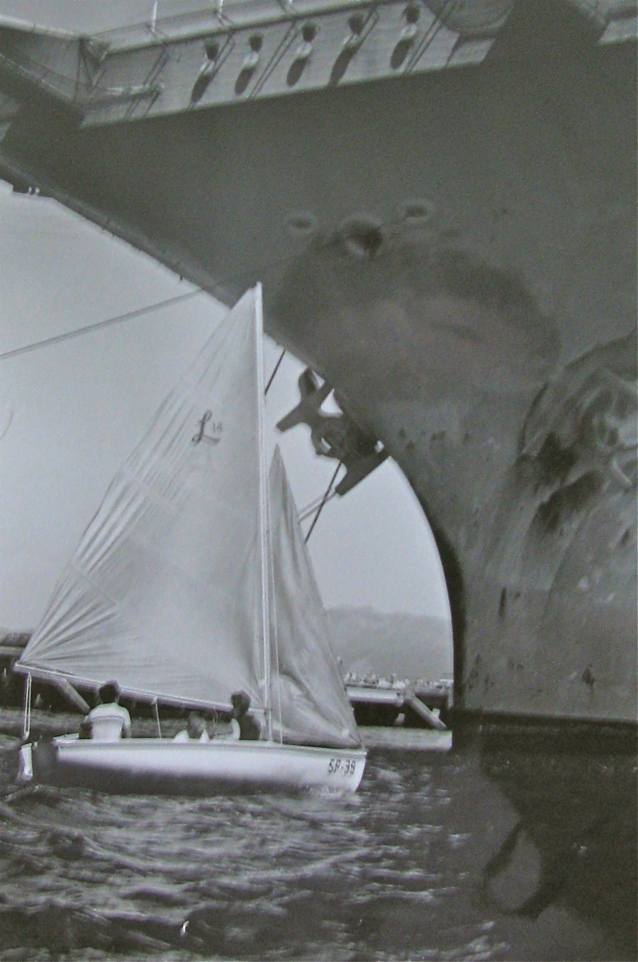 Hyde and his wife, Linda, sail under the bow of a giant aircraft carrier moored at Subic Bay in the Philippines. This is where the Naval officer learned to sail on this 14 Lido Class sloop. Photo provided