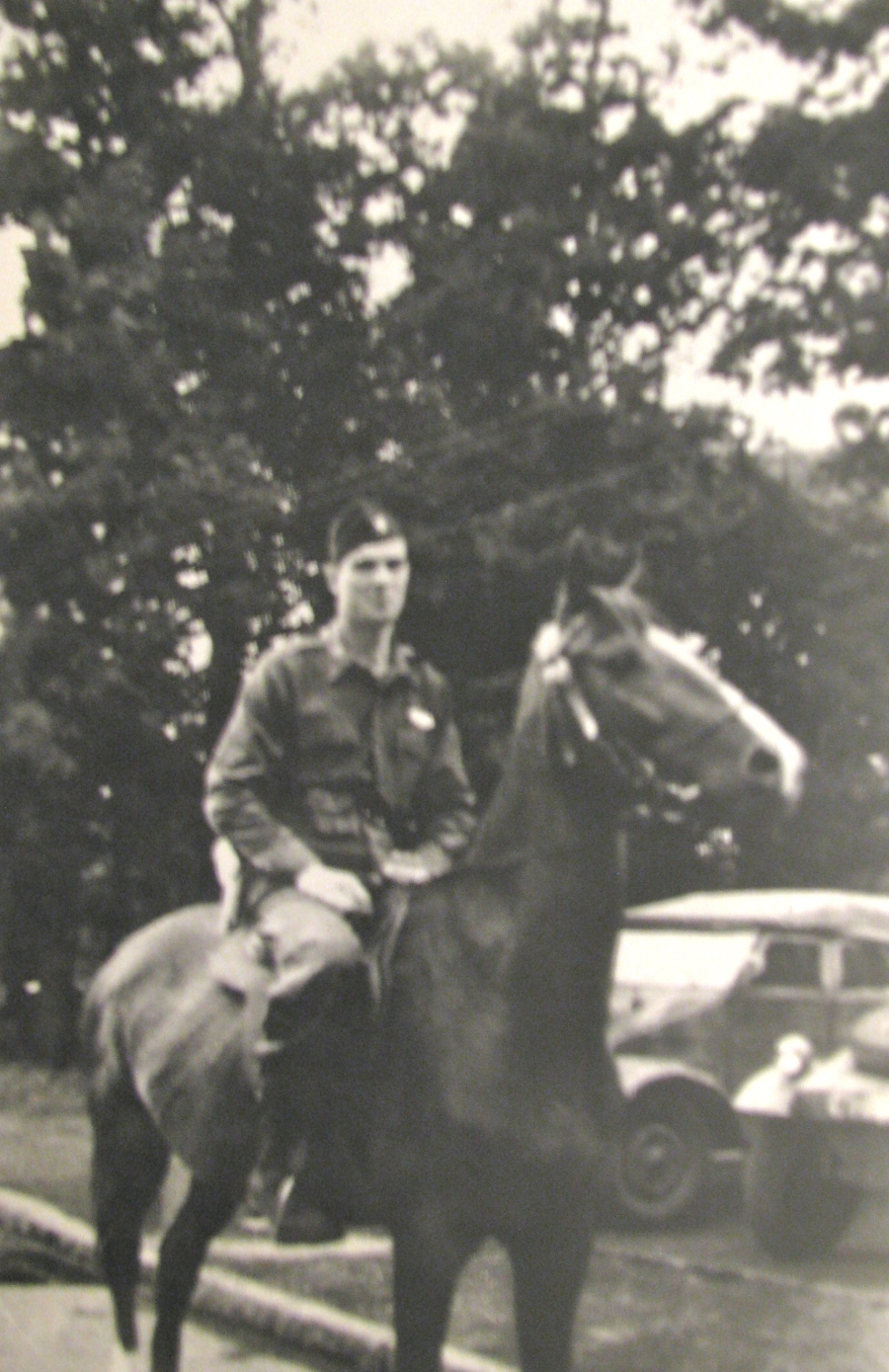 Charles Maloney tries out a horse he had corralled in a POW camp he operated in Alsfeld, Germany. The horse belonged to one of the six captured German generals in the camp. Note the Volkswagens in the background. Photo provided