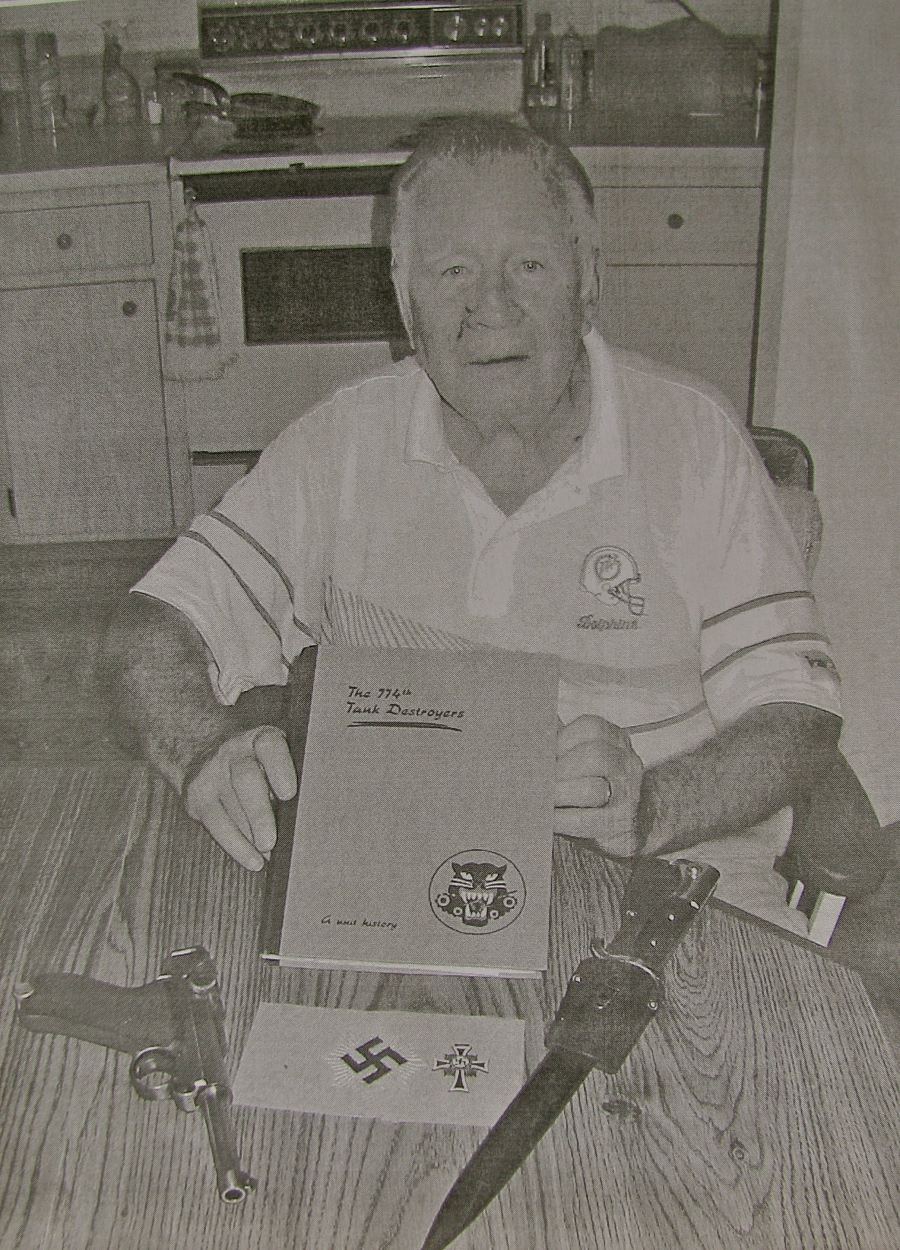 "Les Barth of Port Charlotte holds a copy of a book about the 774th Tank Destroyer Battalion he served in during World War II attached to Patton's 3rd Army. On his dining room table at left is a German Luger pistol he ""liberated"" from a dead German officer. At right is a German dress bayonet. The Nazi armband in the foreground was taken from a Nazi headquarters. Sun photo by Don Moore"
