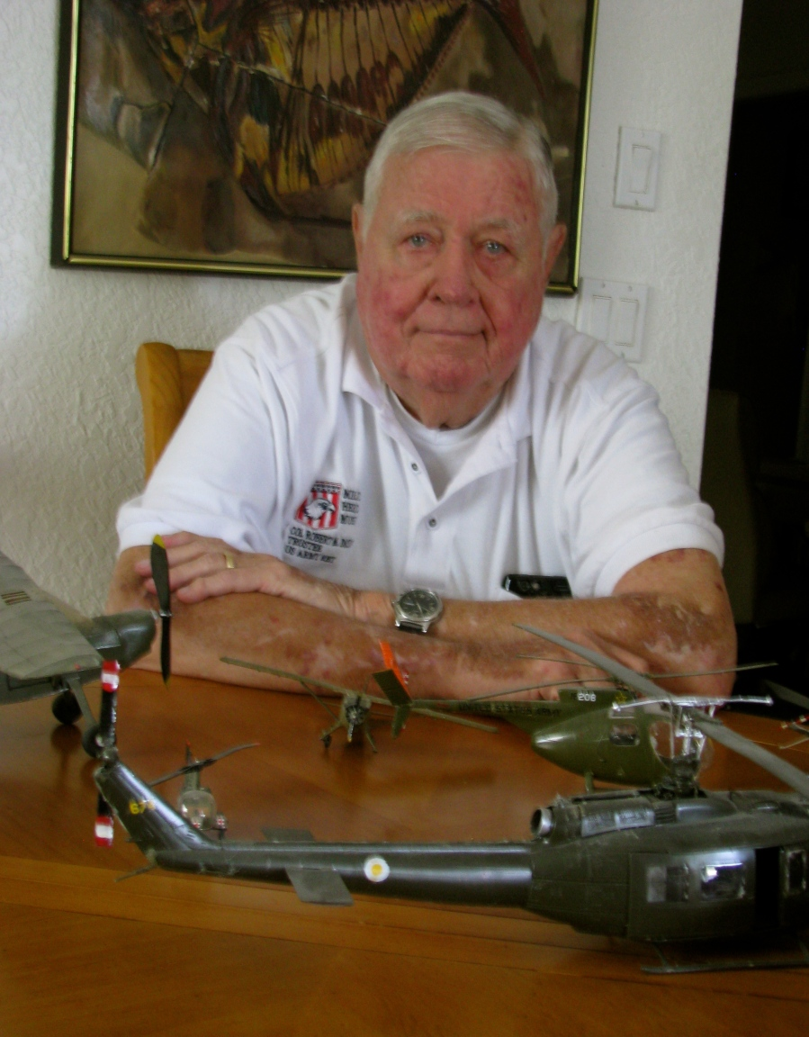 Dickinson sits in front of some of the models of fixed wing planes and helicopters he flew during his decades of service in Army aviation. Sun photo by Don Moore