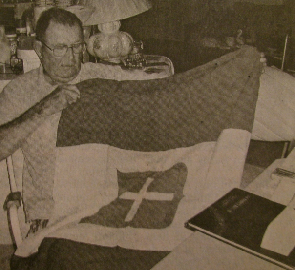"Paul Grube looks at an Italian battle flag he ""liberated"" from a captured Italian officer while fighting in North Africa during World War II. Sun photo by Don Moore"