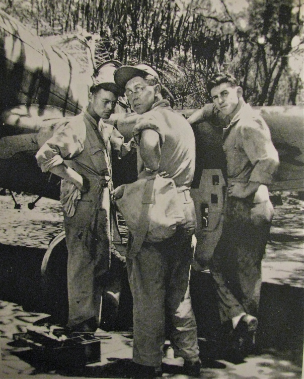 "Sherick (L) talks to a couple of his buddies working on a P-40 ""Tomahawk"" fighter plane."