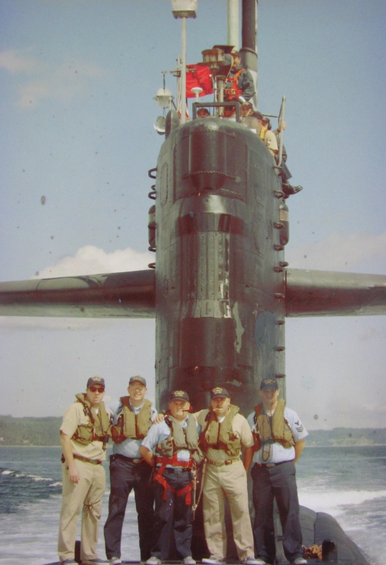 Sanzalone, fourth from the left, stands on the deck of the USS Pache (SSN-683) with a cigar in his mouth, along with the sub's officers after the attack submarine surfaced during sea trials off Bangor, Wash. in 2003. Photo provided