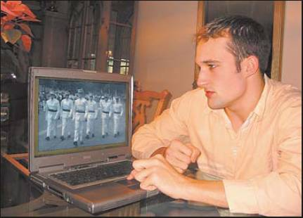 Bryan Coward looks at a photo of himself and other members of his junior year class at Wst Point. They're in their summer dress uniforms marching at the head of a parade at the end of basic training. Bryan is second from left in the photo on his computer screen. Sun photo by Don Moore