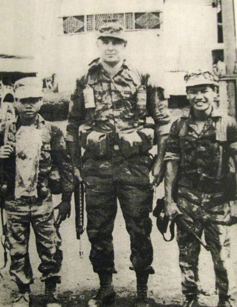 "He towers over a couple of his Montagnard commandos while serving in Laos during the ""Secret War"" of the early 1970s. The little commando on his right was Poole's radio operator. The commando on his left was his interpreter. Photo provided"