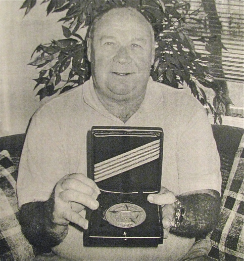"Tom Poole holds his massive ""Intelligence Star"" medal he received from the CIA for his outstanding work commanding three Thai mercenary battalions in the 1972 ""Easter Offensive"" during the ""Secret War"" in Laos. Sun photo by Don Moore"