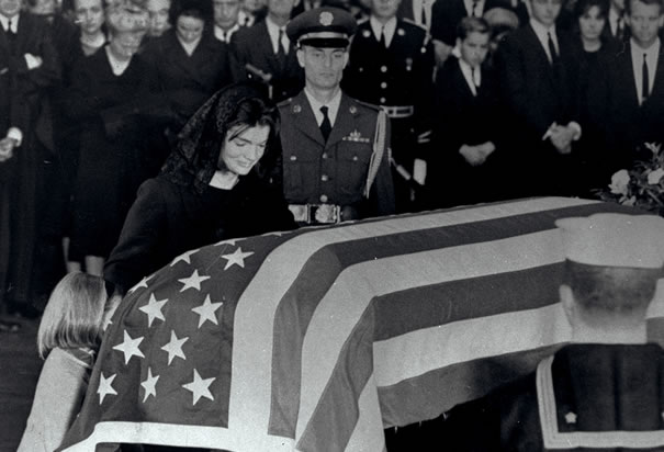 First Lady Jacqueline Kennedy kneels beside the coffin of her slain husband in the Rotonda of the capitol.