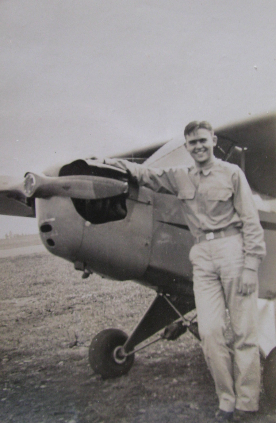 Cunningham is all smiles as he leans against a Piper Cub he soloed in during early flight training in the snow at Siena College in New York during the winter of 1942. Photo provided