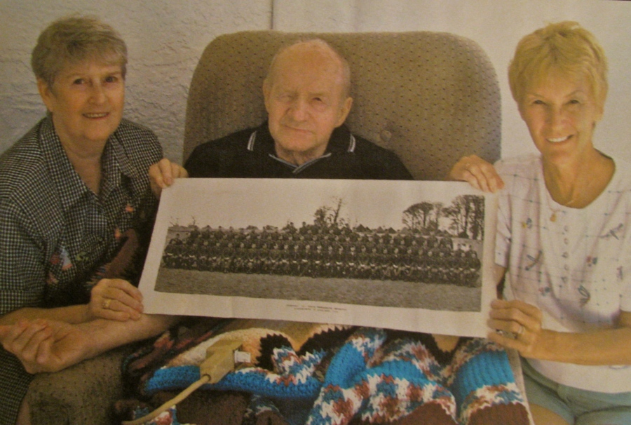 Former Pvt. Arvith Hamilton of Burnt Store holds a picture of A-Company, 502nd Parachute Infantry somewhere in England in 1944. He is pictured among the soldiers who were part of the original 101st Airborne Division. His wife. Lucille, left, and his daughter, Dawn Thurlow, of Punta Gorda, hold both ends of the picture. Sun photo by Don Moore