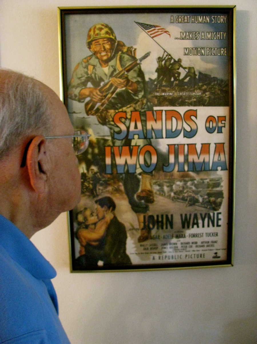 """Leon Gumley of Sarasota looks at a movie poster on his living room wall advertising """"Sands of Iwo Jima"""" in which he played in with John Wayne after being a glider pilot in World War II. Sun photo by Don Moore"""