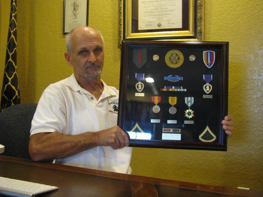 Ron Heurlin today at 66 at his home in Punta Gorda Isles. He's holding a shadow box that contains: Two Purple Heart medals, Combat Infantryman's Badge, National Defense Service Medal and Vietnamese Campaign Medal he received for serving in the Vietnam War. Sun photo by Don Moore