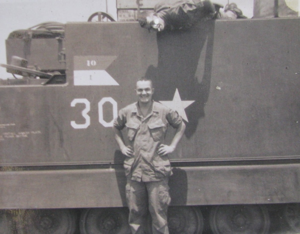 Behind Mac Lellan is an armored personnel carrier he was in charge of during part of the time he spent in the Central Highlands in Vietnam. Photo provided