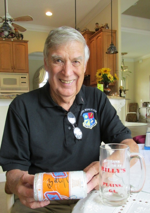 """Laurent holds an autographed can of """"Billy Beer"""" he received from President Jimmy Carter's brother. The beer stein on the table is inscribed: """"I drank a beer at Billy's, Planes, Ga."""" Sun photo by Don Moore"""