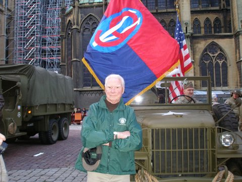 Glenn Magner holds a 95th Infantry Division banner in the town square at Metz, France during the 65th anniversary of the Battle of Metz in World War II. He and his wife, Lee Ann, plan to be in Metz this fall for the 70th anniversary of the battle. Photo provided