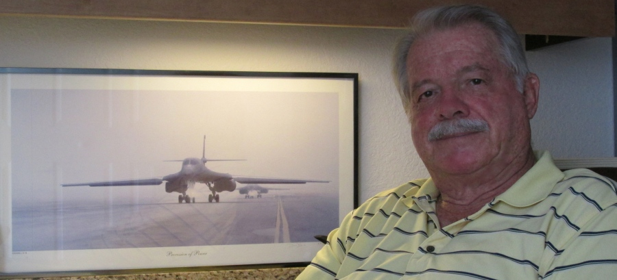 Chet Buckenmaier of Burnt Store Marina sits beside a picture of a B-1 Bomber he helped design and build while serving in the Air Force for almost 20 years. Sun photo by Don Moore