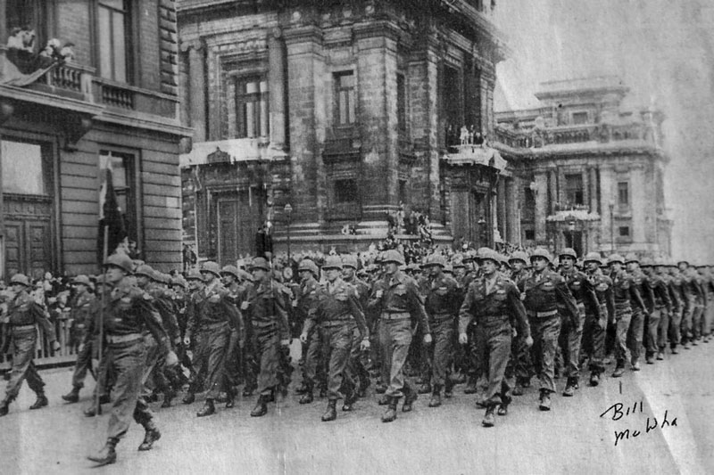 On parade: Soldiers in the 35th Infantry Division put on a parade in Belgium after the war for President Harry Truman. Pfc. William McWha of Englewood is in the middle of the line of marching soldiers on the end. The notation at the bottom of the picture points him out.
