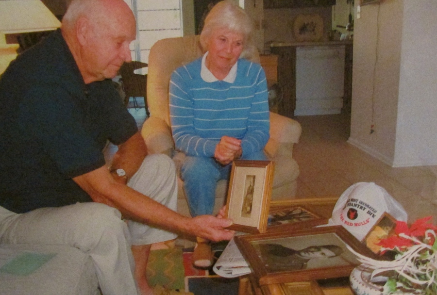 Jollay and his wife, Sammy, look at war photos of himself when he was a member of the 34th Infantry Division during World War II. Sun photo by Don Moore