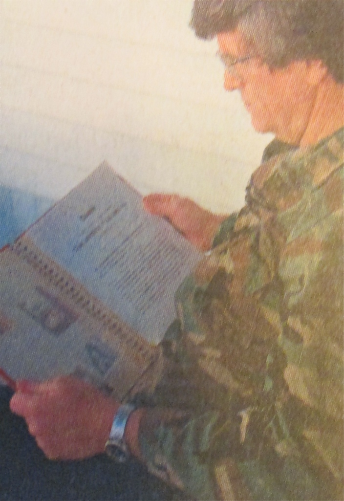 Lee St. John of Arcadia looks at his scrapbook from Vietnam. On the right is the Bronze Star citation he received while working for a secret communications outfit in 'Nam.  Sun photo by Don Moore